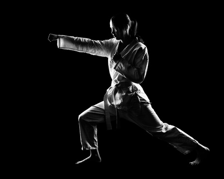 full-length silhouette portrait of beautiful martial arts girl in kimono excercising karate kata on black