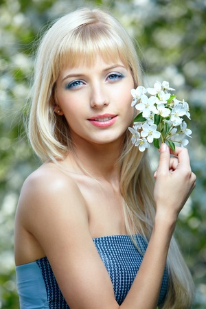 outdoor portrait of happy beautiful blue-eyed blonde girl posing with flowers in her hair