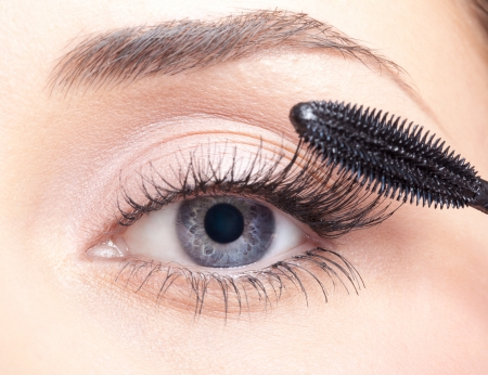 Young beautiful woman applying mascara makeup on eyes by brush