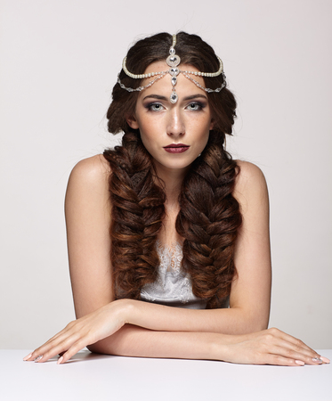 Beauty portrait of young woman in pearl diadem. Brunette girl with braids hairdo and day female makeup sit at white table on gray background.