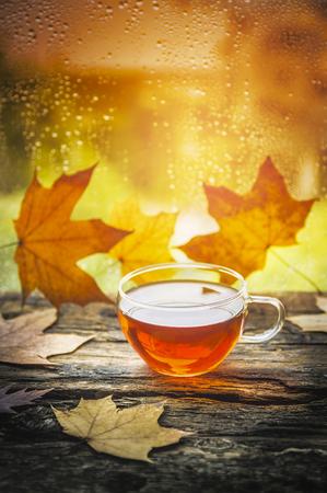 Foto de cup of tea on a wooden window sill with autumn leaves against the window with raindrops - Imagen libre de derechos