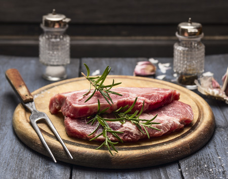 Foto de raw meat with rosemary, garlic, salt and pepper on a wooden board with a fork - Imagen libre de derechos