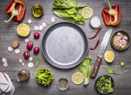 Foto per concept cooking vegetarian food ingredients laid out around the pan with a knife and spices space for text on rustic wooden background top view - Immagine Royalty Free