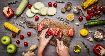Female hand cut tomatoes on rustic kitchen table, around lie ingredients, vegetables, fruits, and spices, Healthy foods, cooking and vegetarian concept.