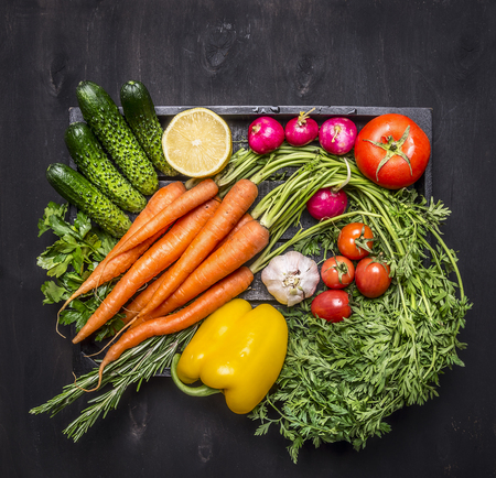 Colorful various of organic farm vegetables in a wooden box on wooden rustic background top view close up