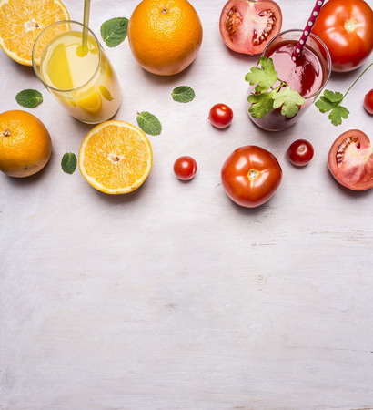 fresh tomato and orange juices with mint in glasses with straws border, place for text on wooden rustic background top view close up