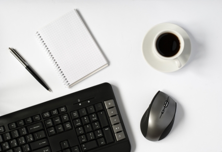 Overhead view of an office work station with a wireless computer mouse, keyboard, a cup of espresso coffee and a blank notebook and pen on a white surface