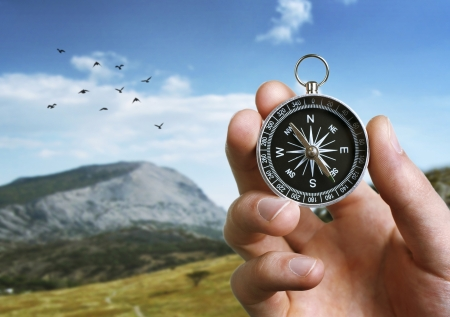 Foto de Close up of the hand of a man holding a magnetic compass over a landscape view as he uses it to navigate when exploring or travelling in the countryside - Imagen libre de derechos