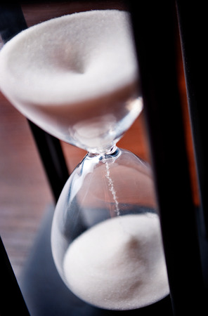 High angle close up view of sand running through an hour glass or egg timer measuring the passing time and counting down to a deadline