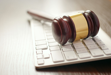 Photo pour Wooden gavel with a brass decoration lying on a computer keyboard conceptual of online auctions or law enforcement - image libre de droit