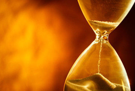 Photo pour Sand passing through the glass bulbs of an hourglass measuring the passing time as it counts down to a deadline or closure on a yellow background with copyspace - image libre de droit