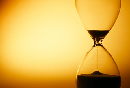 Foto de Sand passing through the glass bulbs of an hourglass measuring the passing time as it counts down to a deadline or closure on a yellow background with copyspace - Imagen libre de derechos