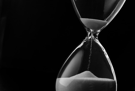 Foto de Sand running through the bulbs of an hourglass measuring the passing time in a countdown to a deadline, on a dark background with copyspace - Imagen libre de derechos