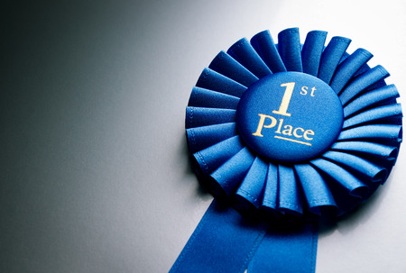Photo pour Blue first place winner rosette or badge from pleated ribbon with central text to be awarded to the winner of a competition on a graduated grey background with copyspace - image libre de droit