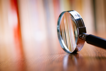 Photo for Close up Single Magnifying Glass with Black Handle, Leaning on the Wooden Table at the Office. - Royalty Free Image