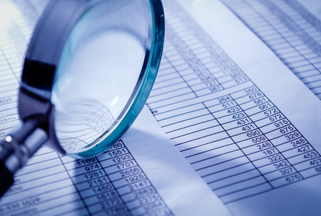 Photo pour Conceptual Magnifying Glass on Top of Sales Invoice Reports, Emphasizing Scrutinizing Figures. - image libre de droit