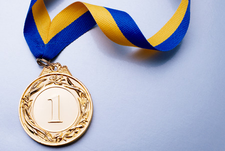 Photo pour Gold medal in the foreground on yellow blue ribbon - image libre de droit