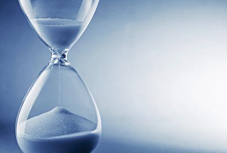 Foto de Closeup hourglass clock on light blue background - Imagen libre de derechos