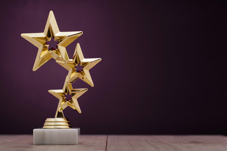 Foto de Gold winners award with three stars to be awarded to the first place in a competition or championship standing on a pedestal against a purple background with copy space - Imagen libre de derechos