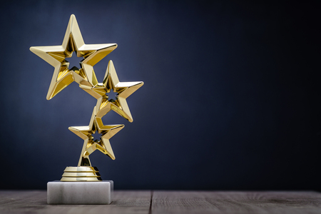 Photo pour Gold winners award with three stars to be awarded to the first place in a competition or championship standing on a pedestal against a blue background with copy space - image libre de droit