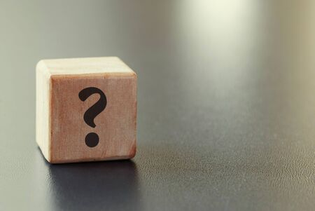 Photo pour Small wooden toy block with question mark over a grey background with highlight and copy space in a conceptual image - image libre de droit
