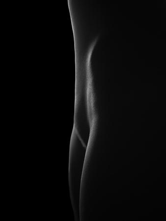 Foto de Nude female legs   isolated at black - Imagen libre de derechos