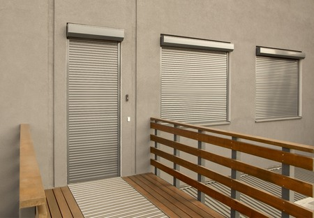 Photo pour Light brown metal blinds on the doors and windows of the house - image libre de droit