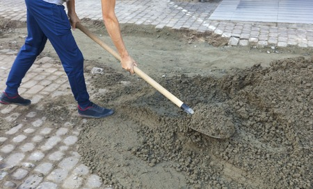 Foto de The worker level the foundation with mortar and shovel for repairing the sidewalk pavement tile - Imagen libre de derechos