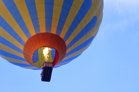 Foto de The flame of fire heats the air in a motley yellow-blue beautiful balloon and raises a basket of tourists to the blue sky, view from below. - Imagen libre de derechos