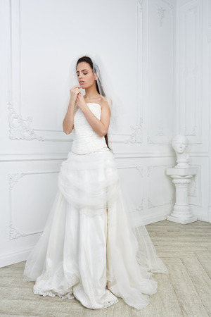Photo pour Slim beautiful young woman posing in a wedding dress in studio - image libre de droit