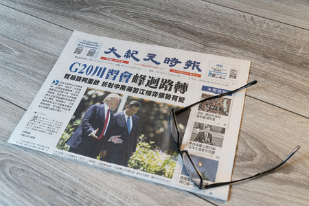 Foto für Udine, Italy. July 15, 2019.  The lecture of the Chinese Epoch Times newspaper on a wooden table - Lizenzfreies Bild