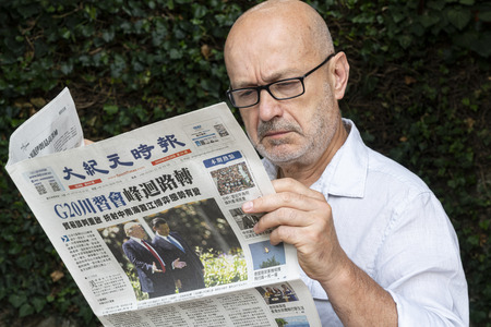Foto für Udine, Italy. July 15 2019.  a western man reading the Chinese Epoch Times newspaper - Lizenzfreies Bild