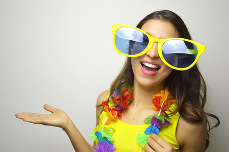 Photo pour Carnival time. Young woman with big funny sunglasses and carnival garland smile at camera and show your product or text on gray background. - image libre de droit