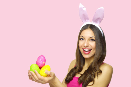 Photo pour Happy Easter concept. Happy cheerful woman with bunny ears holding colorful Easter eggs looking at camera over pink background. Copy space. - image libre de droit