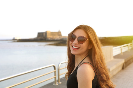 Photo pour Young pretty smiling woman in black tank top and sunglasses at sunset - image libre de droit