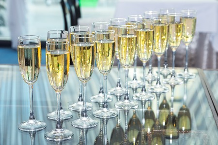 Photo for Elegant glasses with champagne standing in a row on serving table during party or celebration - Royalty Free Image