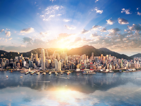 Foto de Hong Kong city skyline view from harbor with skyscrapers buildings reflect in water at sunset with sunlight and sun rays shine through clouds on blue sky - Imagen libre de derechos