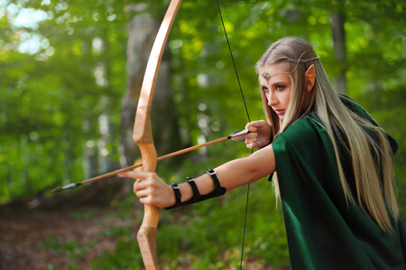 Photo for Beautiful female elf archer in the forest hunting with a bow - Royalty Free Image