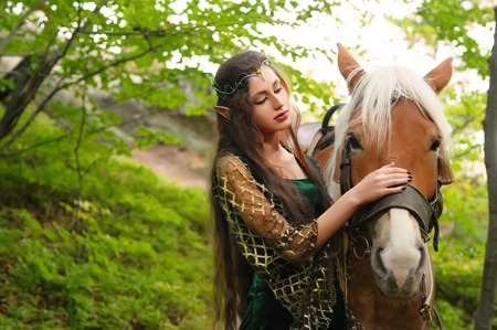 Photo for Female elf in the forest with her horse - Royalty Free Image