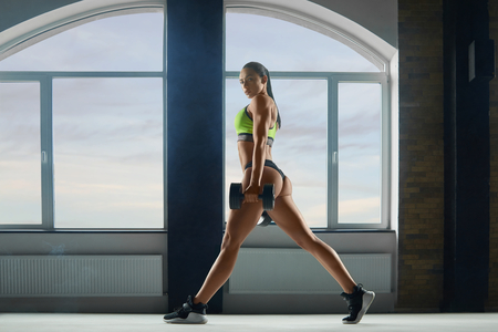 Foto de Sporty woman with strong body making exercises in spacy hall with panoramic windows. looks fit and stunning. Beatiful face, powerful muscles. Keeping big dumbbells. Wearing stylish sportswear. - Imagen libre de derechos