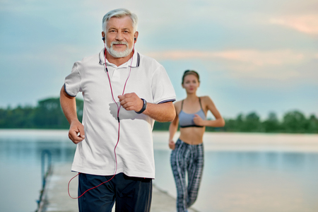 Foto de Senior man listening music, running near lake in evening. Young girl running behind. Outdoor activities, healthy lifestyle, strong bodies, fit figures. Different generations. Sport, yoga, fitness - Imagen libre de derechos