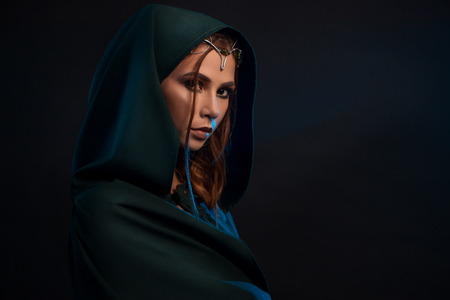 Photo for Beatiful elf princess wearing dark green cape, elegant crown decorated with precious stones, looking at camera from darkness. Girl having pretty face, big eyes, plump lips, long brown hair. - Royalty Free Image