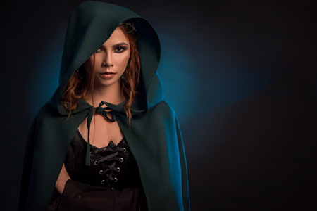 Photo for Mystic girl posing on dark studio background, wearing green cape, black corset. Model looking ar camera, having big eyes, brown curly hair. Looking like musterious elf queen. - Royalty Free Image