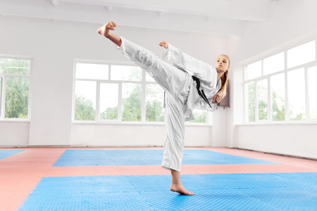 Foto de Sporty karate woman in white kimono with black belt against big window performing martial arts high kick at fight class. Female fighter with blue eyes and braided hair improving technique of fight. - Imagen libre de derechos