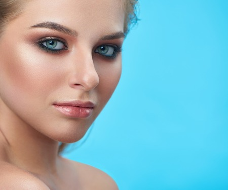 Photo for Portrait of  blond blue eyed girl looking seriosly at camera. Close up of face of pretty beautiful young woman with professional make up and full lips. Isolate of model on blue studio background. - Royalty Free Image