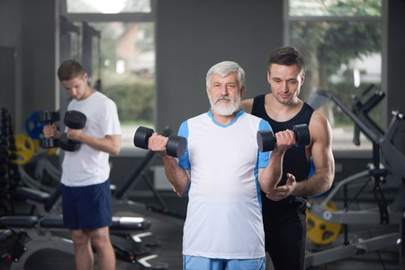 Healthy athletic old man holding dumbbells, looking at camera and posing in gym. Elderly man with gray hair and beard working out in gym. Personal trainer helping man.