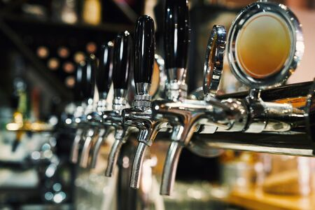 Photo pour Close up of beer taps in row. Metallic equipment for bars and mini brewerys. Concept of modern equipment. - image libre de droit