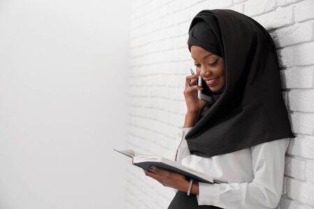 Foto de Cheerful muslim woman standing leaning at white wall, holding notebook and talking by phone. Office worker of company in black hijab looking at notebook, smiling. - Imagen libre de derechos