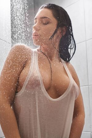 Foto de Portrait of relaxed young woman wearing white wet shirt and taking shower. Hot sexy brunette with big breast enjoying warm water and posing in bathroom. Concept of passion and erotica. - Imagen libre de derechos