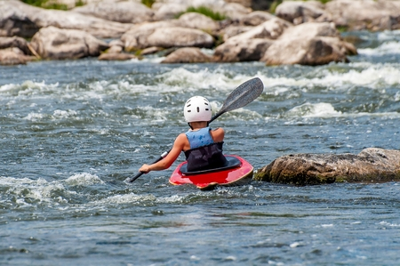 Photo for A teenager trains in the art of kayaking. Slalom boats on rough river rapids. The child is skillfully engaged in rafting. - Royalty Free Image